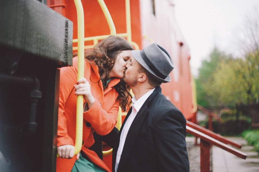 how i met my husband story - girl in orange coat leaning out of vintage train to kiss man in suit jacket and hat