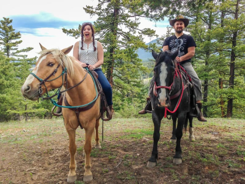 how to afford to travel the world as a couple - husband and wife riding horses in the forest and laughing