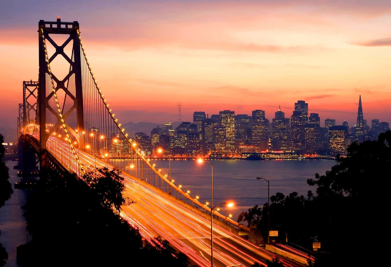 romantic things to do in san francisco header - sunset from behind golden gate bridge city skyline in distance