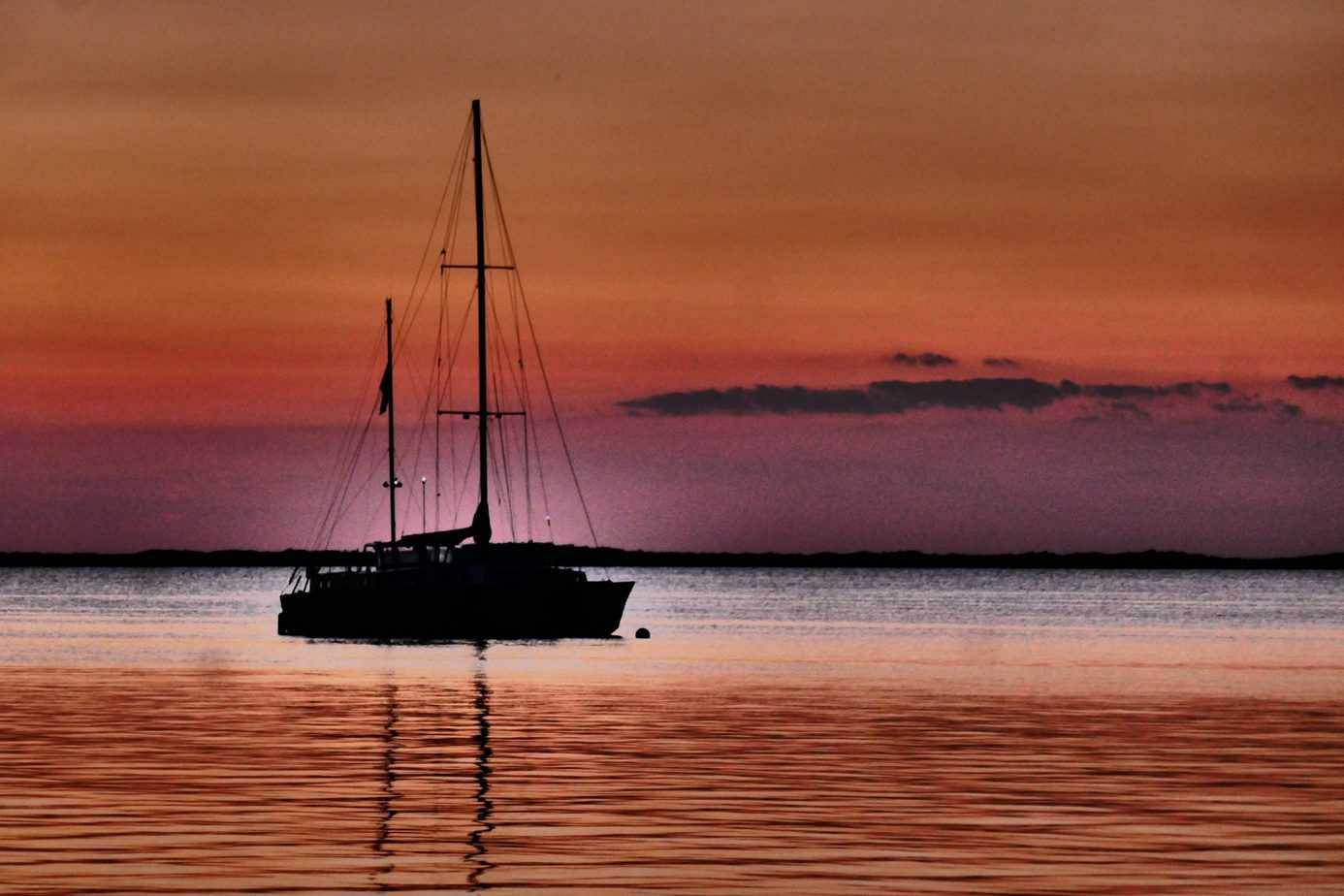 most romantic places to visit in the us - sailboat on water during colorful sunset