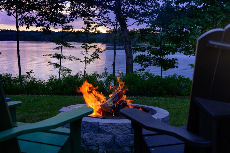couples resorts new england - lakeside fire next to two chairs in maine