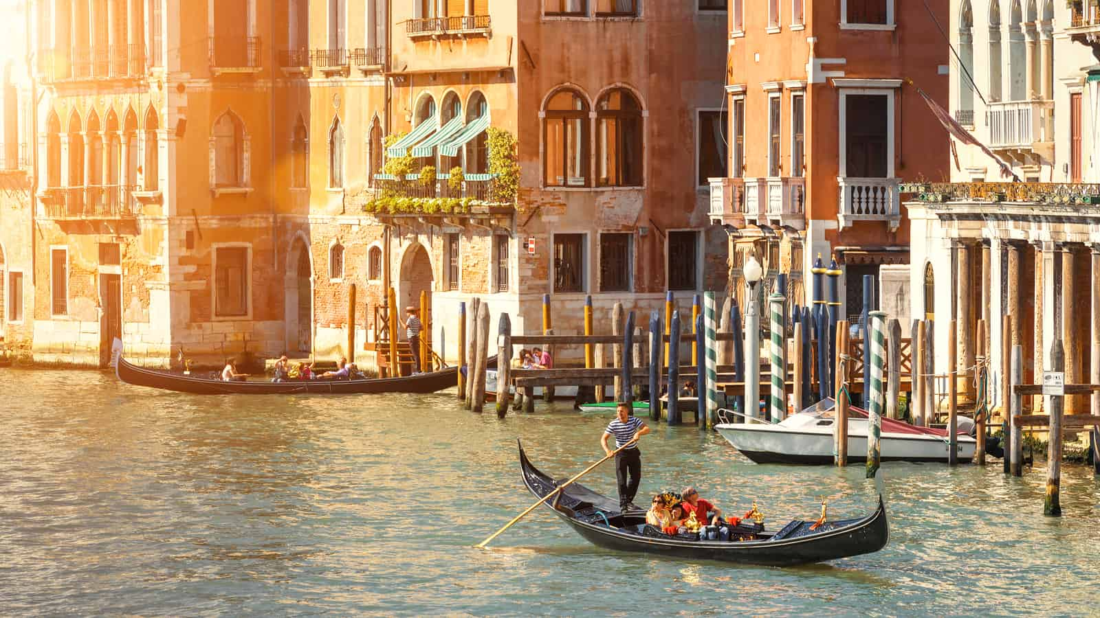 Venice, Italy - May 21, 2017: Gondolas with tourists sailing along the Grand Canal in Venice. Romantic water trip on a gondola in beautiful Venice. Panoramic sunny view of old street of Venice. one of the most romantic things to do in venice