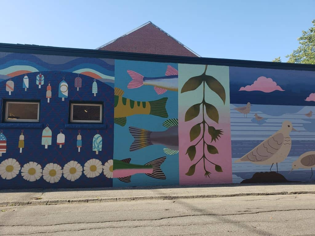 colorful street art in downtown Rockland Maine. an exterior wall painted with pastel colors and shapes including fish, plants, and seagulls