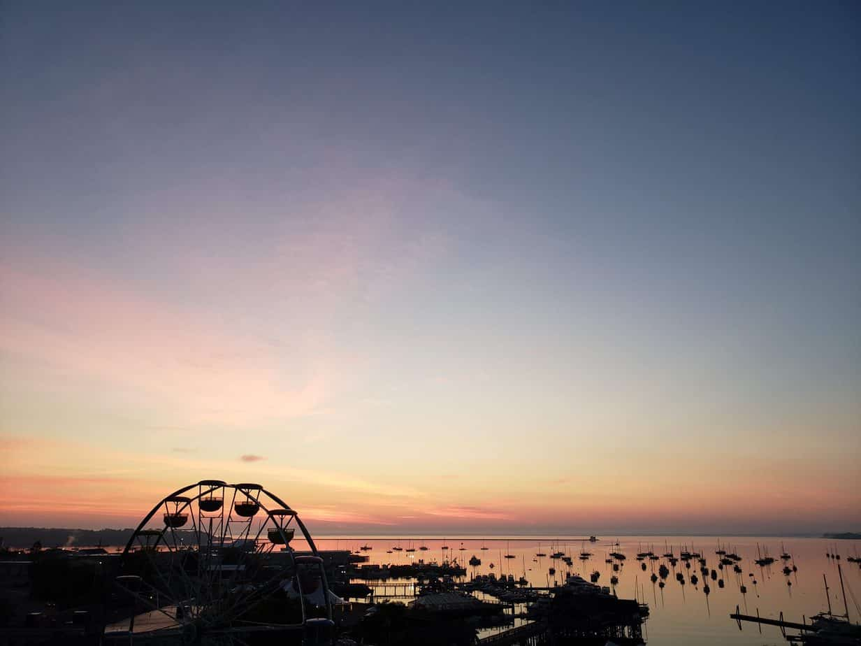 a colorful sunset is seen over a distant Maine harbor with silhouettes of boats and a ferris wheel- things to do in Rockland Maine