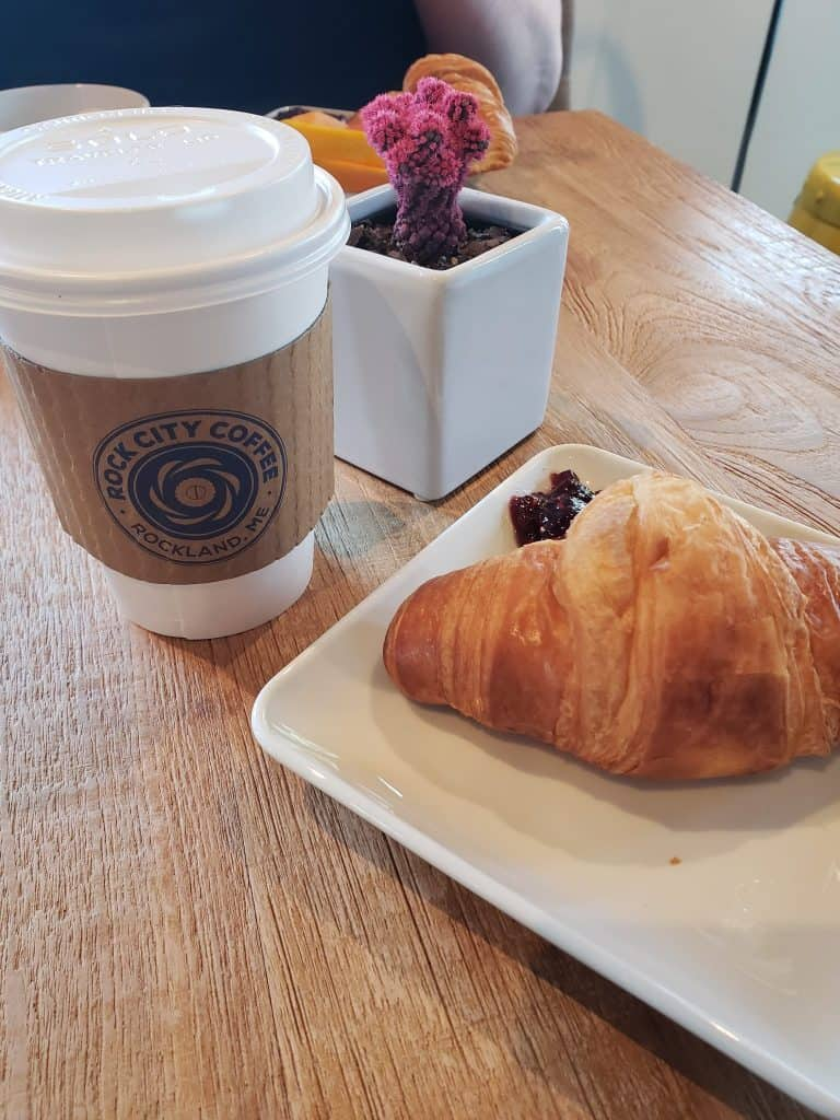 on a table, a croissant next to a white paper coffer cup with a brown label that reads Rock City Coffee