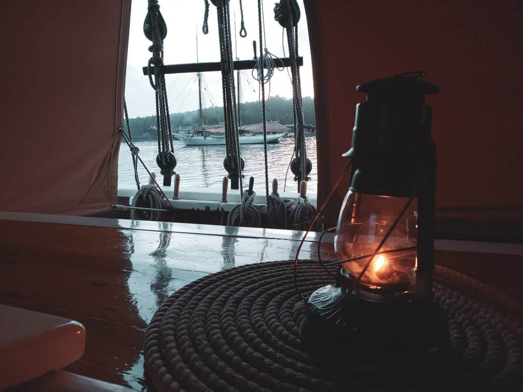 old fashioned lantern on a boat deck with boats and water seen beyond through a gap in the roof canvas