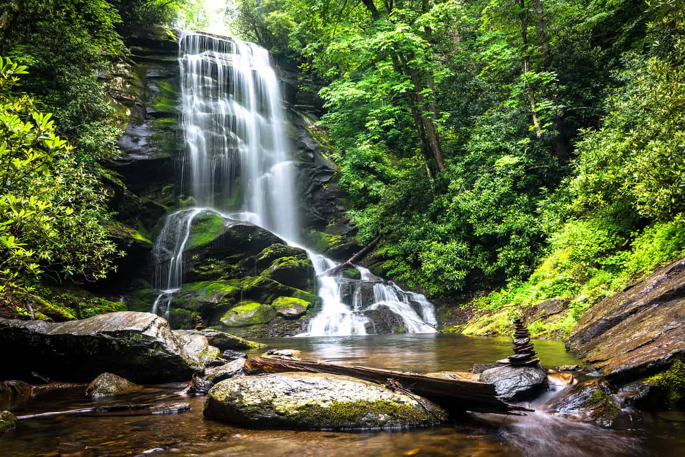waterfall hikes near asheville - image of catawba falls, gentle waterfall over rocks surrounded by green plants