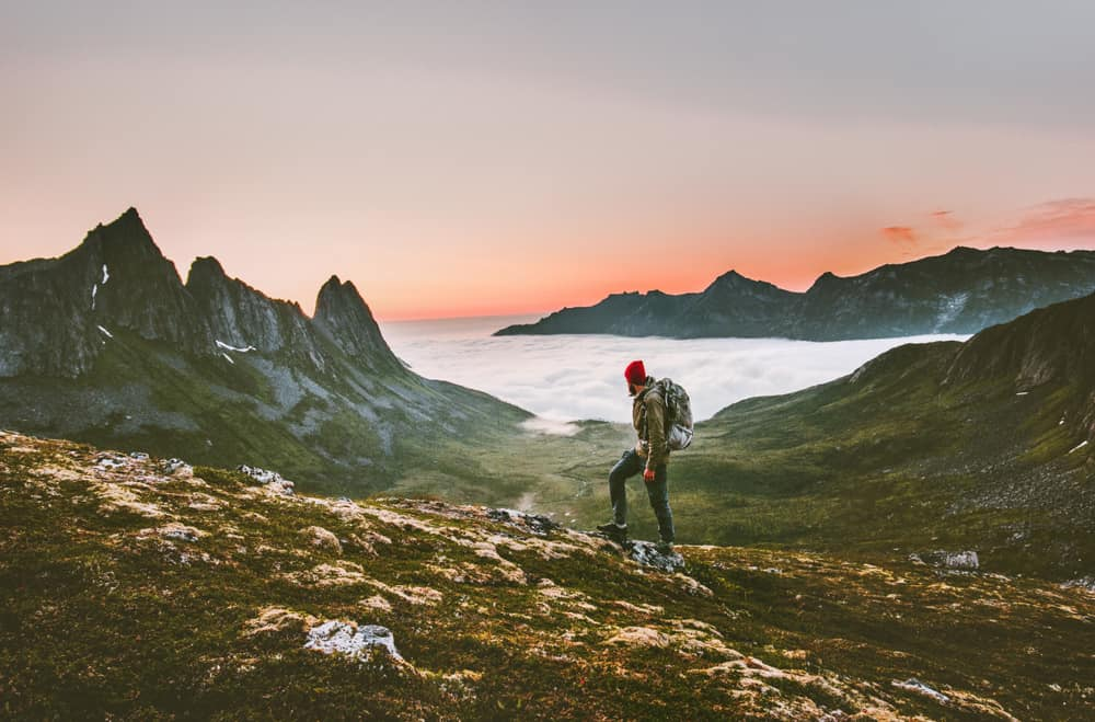 header image best outdoor adventure books - image of male backpacker hiking in Norwegian mountain wilderness at sunset