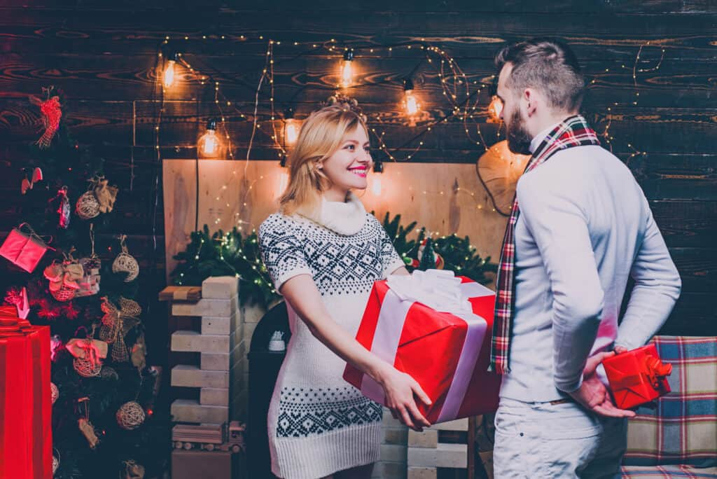 I Love You. Couple In Love. Happy woman and man are giving Christmas gifts to each other. Lovely happy couple. Christmas time. Hapiness