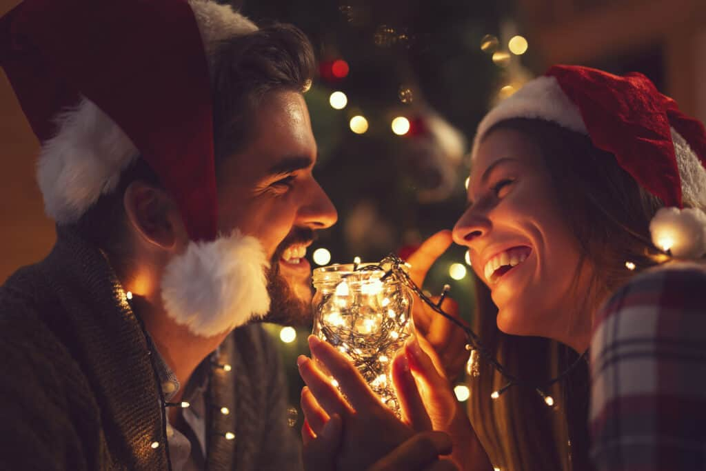 the sweetest christmas gifts for newlyweds -photo of couple smilin in front of lit christmas tree
