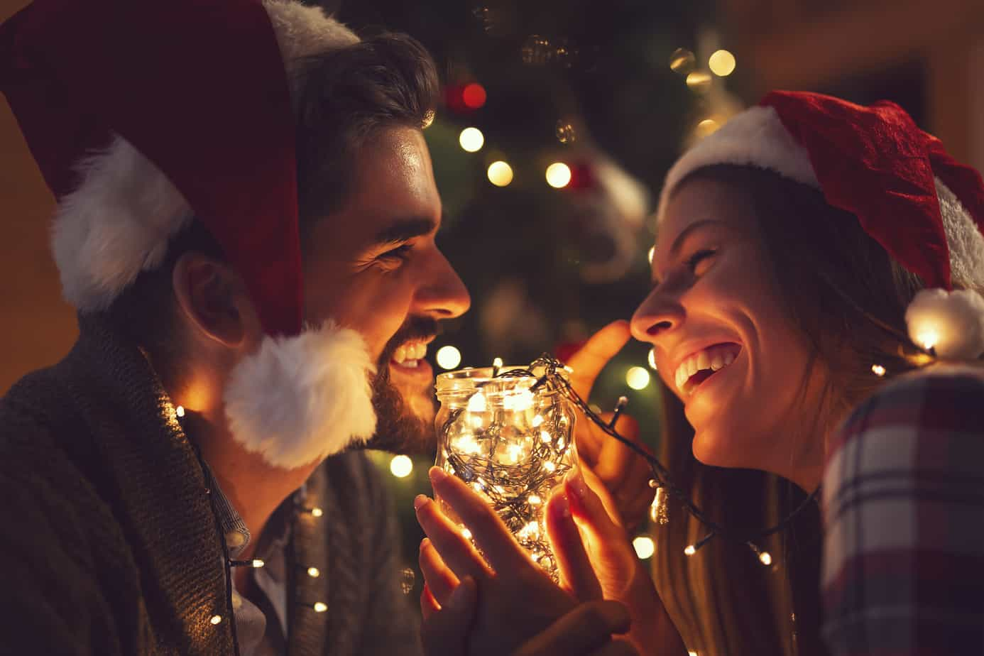 christmas date ideas - photo of couple smilin in front of lit christmas tree