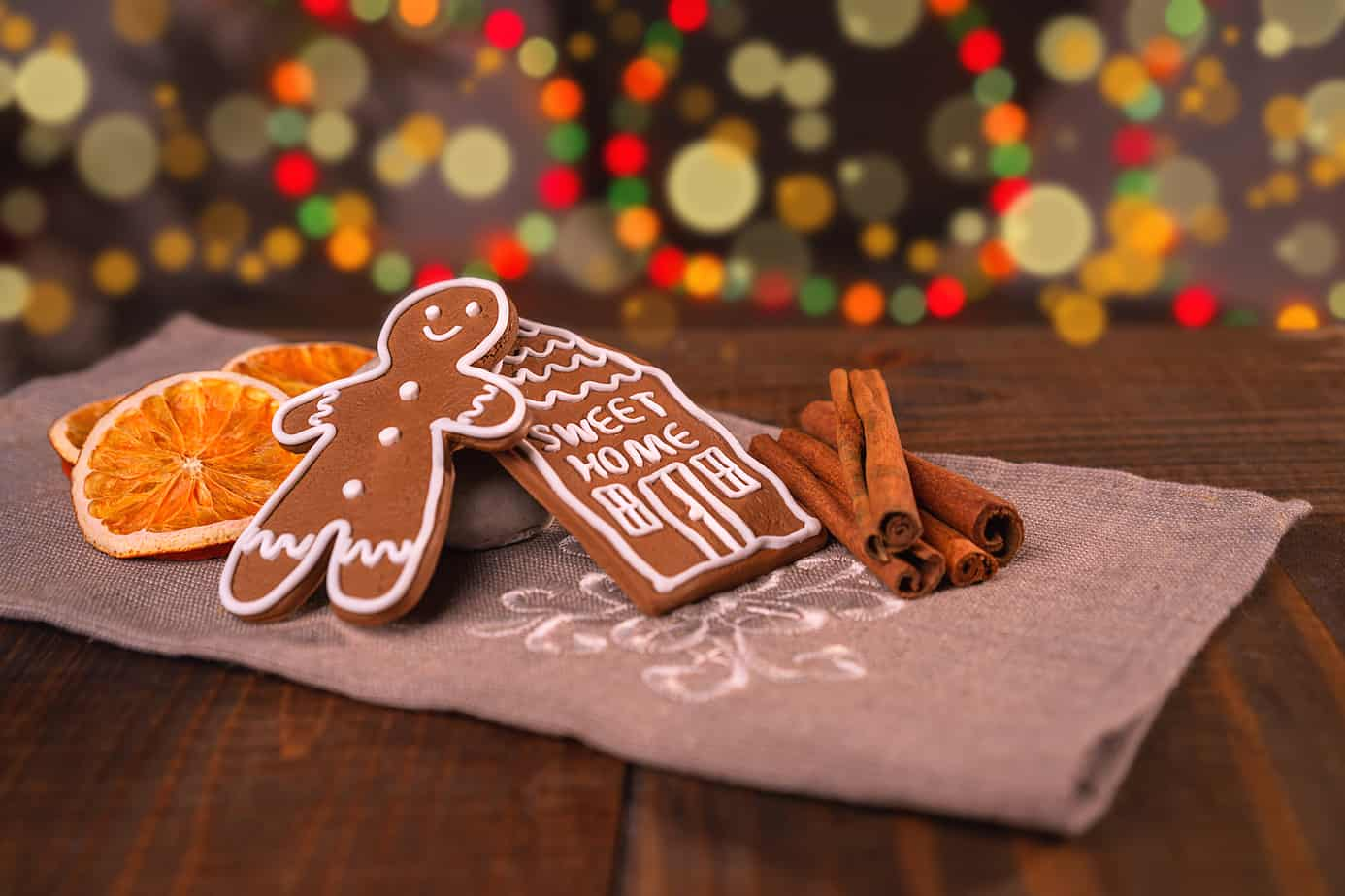Christmas homemade gingerbread cookies on wooden table, slices of dry orange and colored lights on background. gingerbread man house