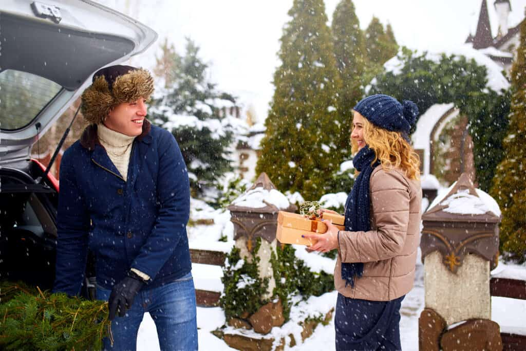 Couple unloading freshly cut down Christmas tree and gift boxes out of car trunk to decorate home. Happy man and woman prepare for New Year holidays together. Snowy winter weather outdoors.