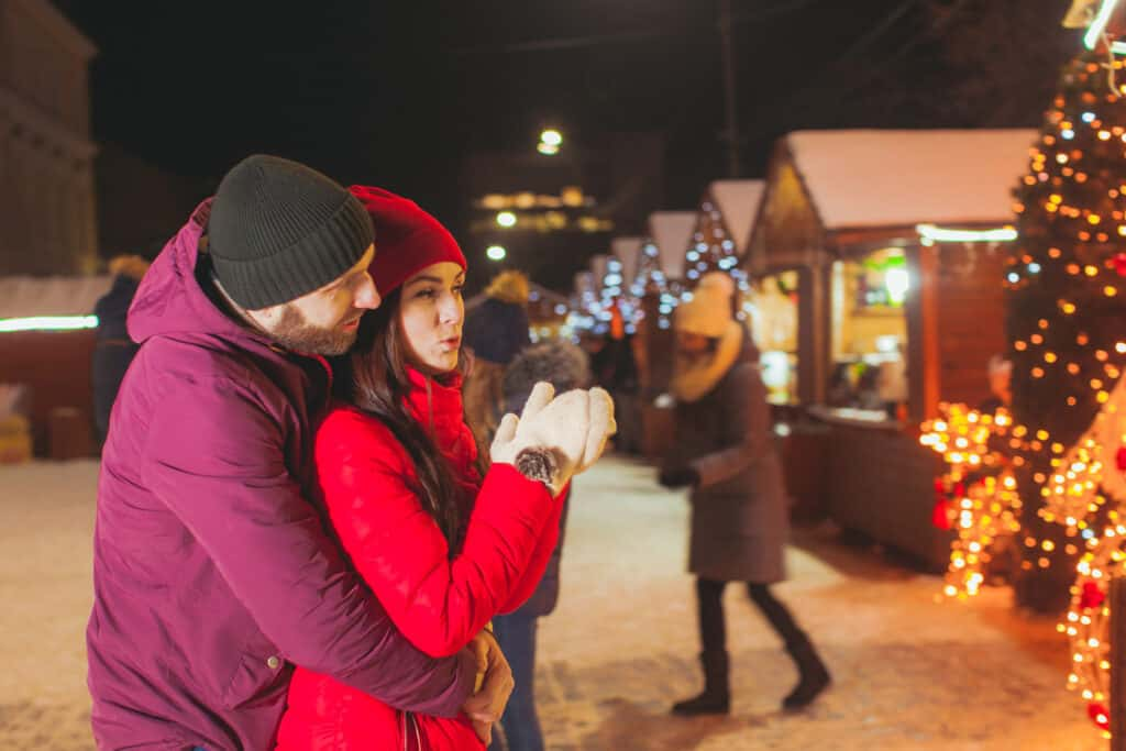 Winter portrait of married couple downtown at night Christmas fair