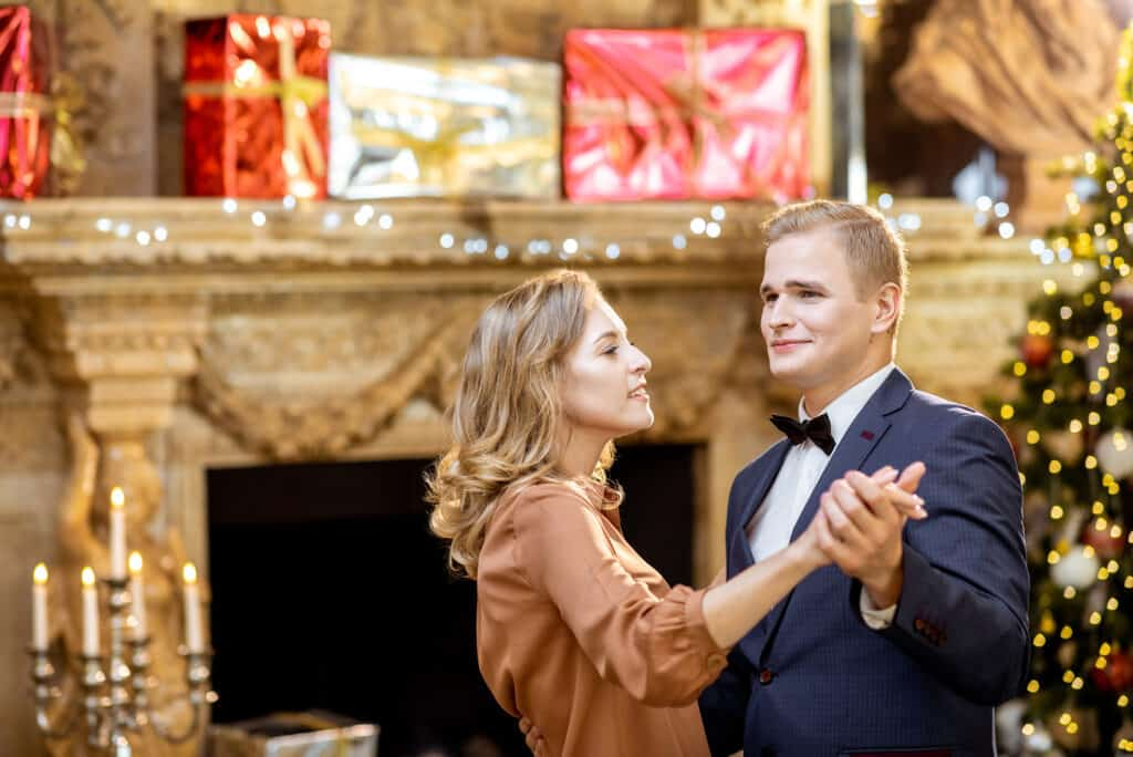 Young well-dressed couple dancing near the christmas tree during the New Year celebration at the beautifully decorated home