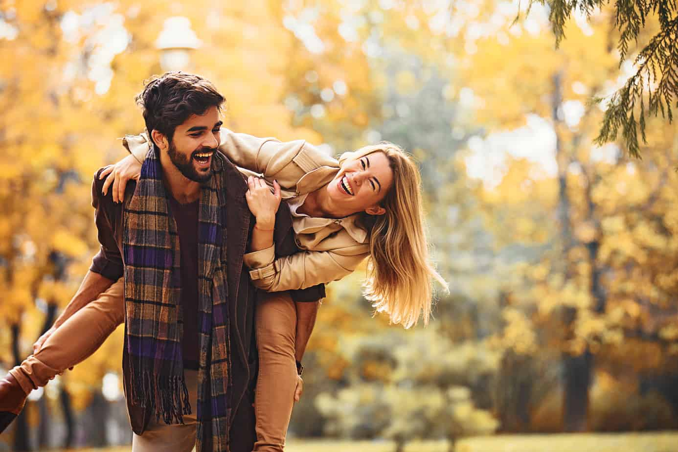 conversation starters for couples image - couple playing in the autumn, blond woman taking piggyback ride from bearded man