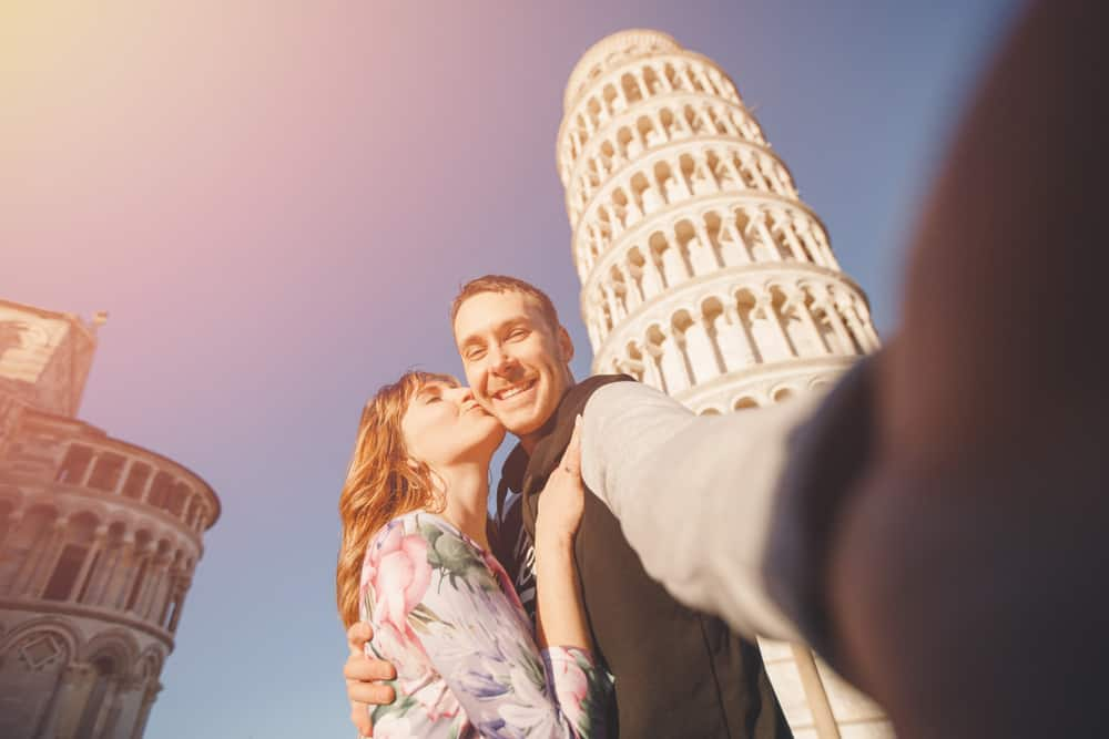 travel is the ultimate relationship test - couple kissing selfie in front of tower of pisa