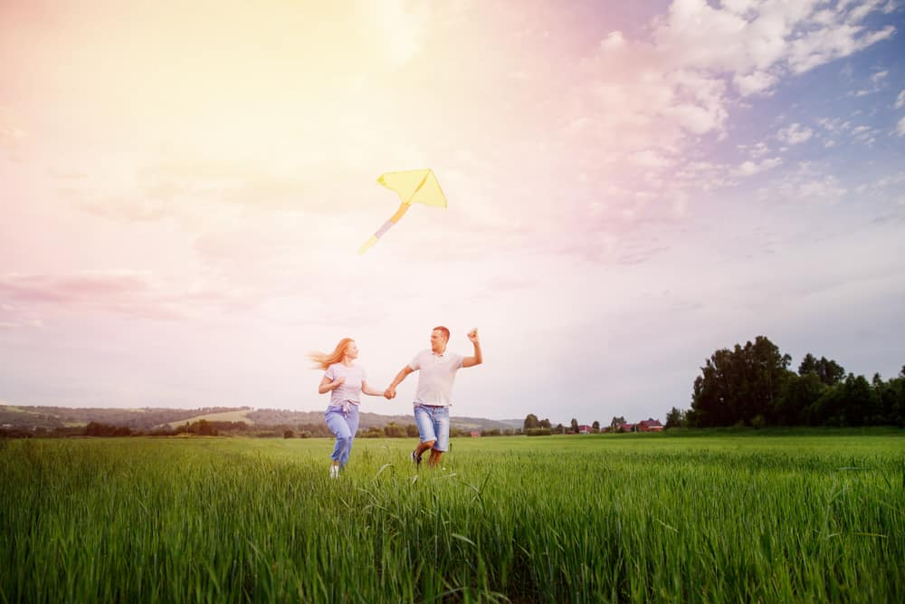 couple flying kite in a field with colorful sky behind them - perfect summer date ideas