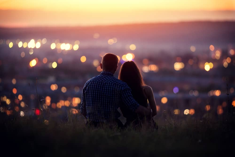 couple sitting and hugging overlooking city at dusk - example of physical touch providing reassurance in a relationship
