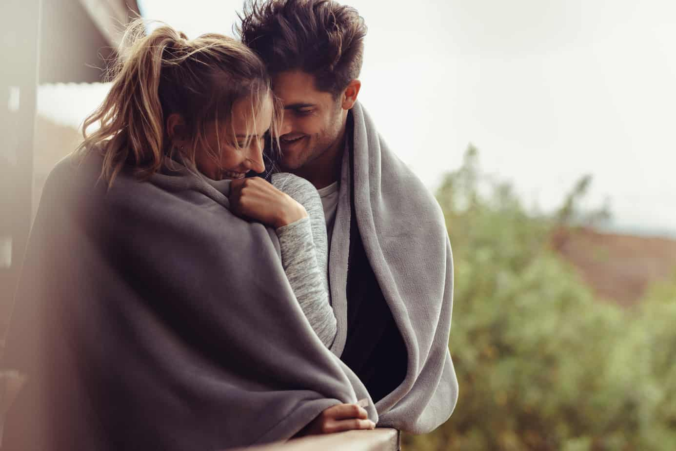 signs you've met the right person header image - photo of cute couple wrapped up together in gray blanket. standing outside on cloudy day