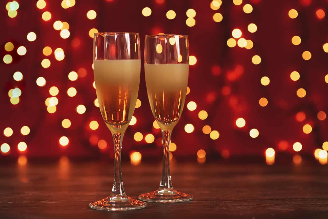 new year's eve date ideas header image - two champagne glasses side by side in front of red background with white lights
