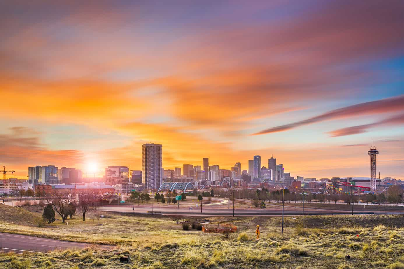 romantic things to do in denver header image - photo of denver skyline at sunset, colorful sky