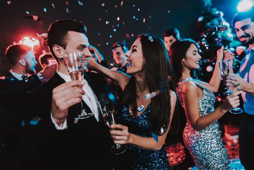 Happy Young People Dancing on New Year Party. Happy New Year Concept. Glass of Champagne. Celebrating of New Year. Young Woman in Dress. Young Man in Suit. Happy People. Modern Dances.
