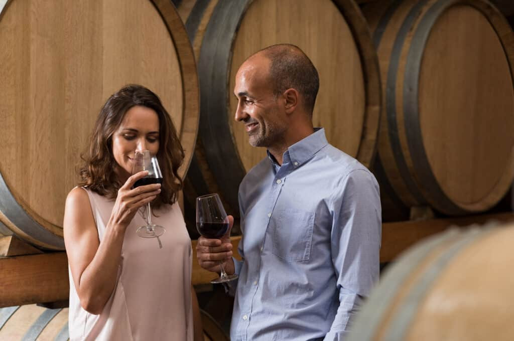 Mature couple tasting a glass of red wine in a traditional cellar