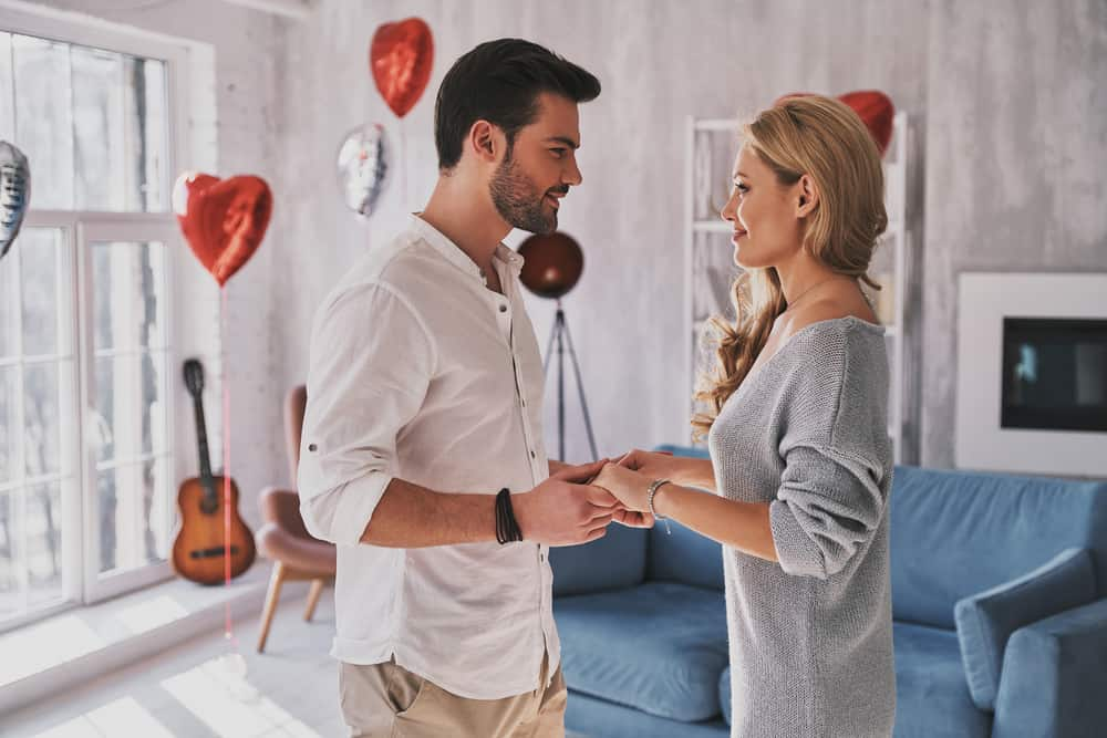 romantic couple holding hands in living room with heart balloons in background - valentines date night
