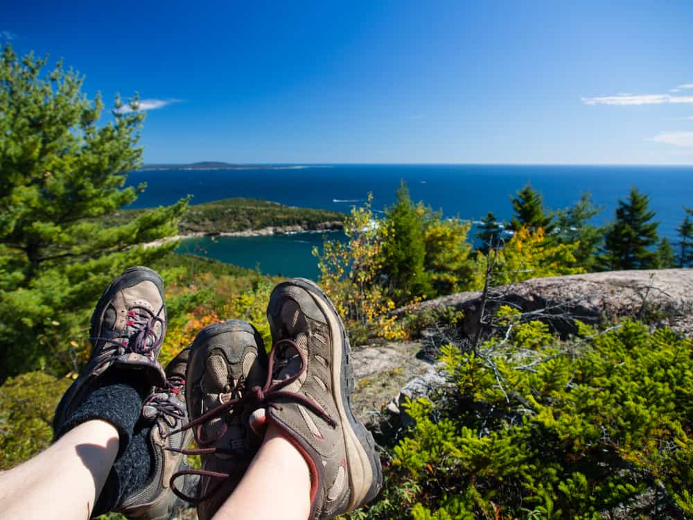 gifts for hikers - photo of two people's feet in hiking boots, looking out over an ocean view from a rocky mountain