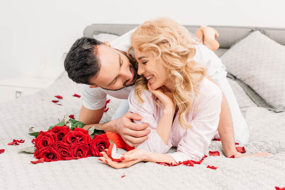 valentine's day date ideas - couple cuddling on bed next to bright red bouquet of roses