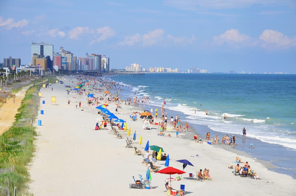romantic myrtle beach getaway - photo of myrtle beach from above, beach filled with umbrellas, water very blue, white sand