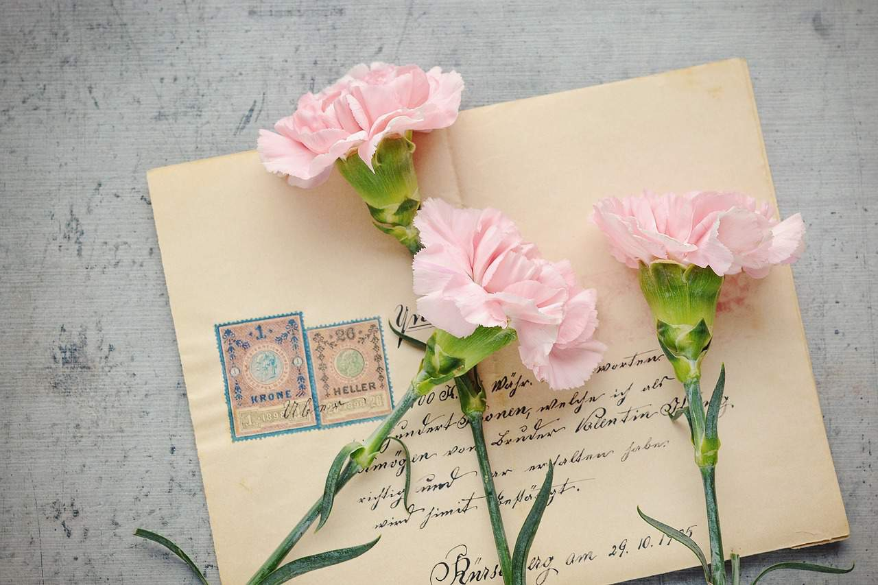 open when letter ideas for couples - image of pink carnations on top of old fashioned envelope