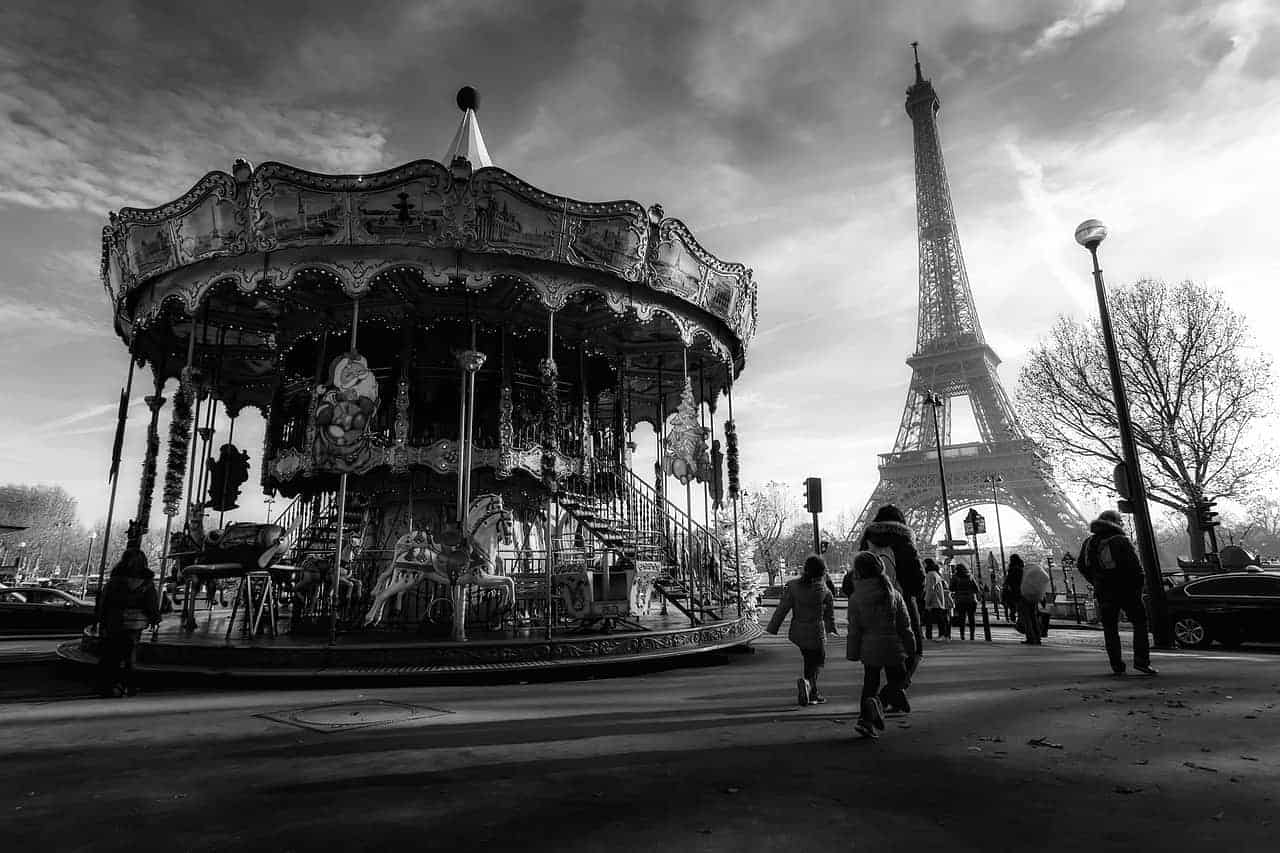 5 days in paris itinerary - a black and white image of a carousel in paris with the eiffel tower in the background