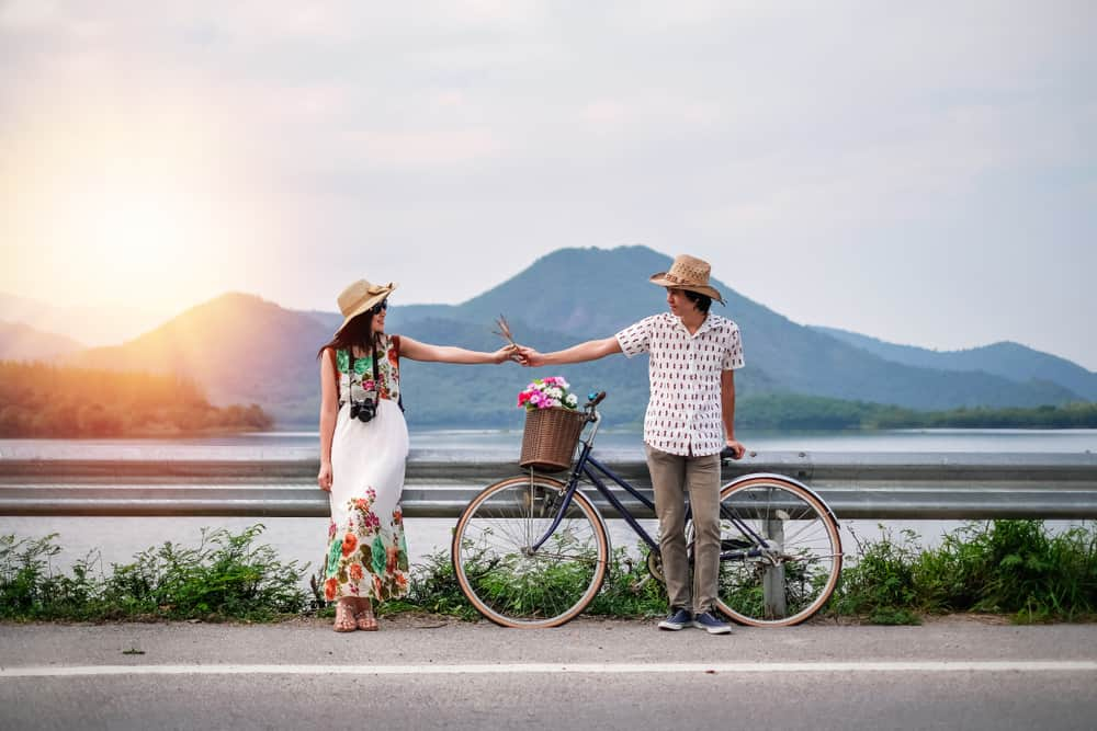 couples travel quotes main image - couple in tropical setting holding hands while standing next to a bicycle. volcano in background