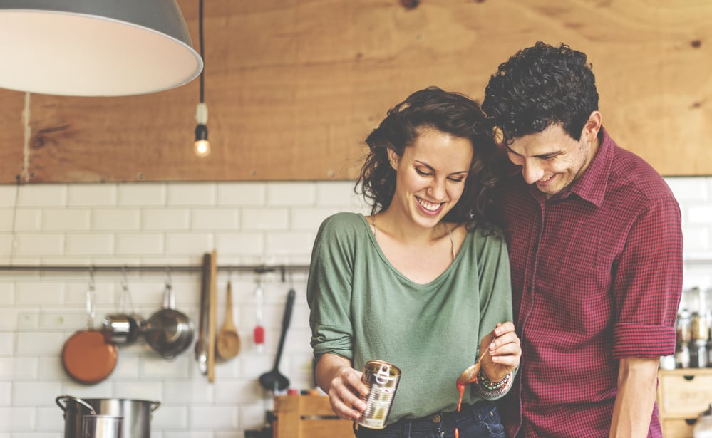 couples communication books - couples standing and smiling together in kitchen