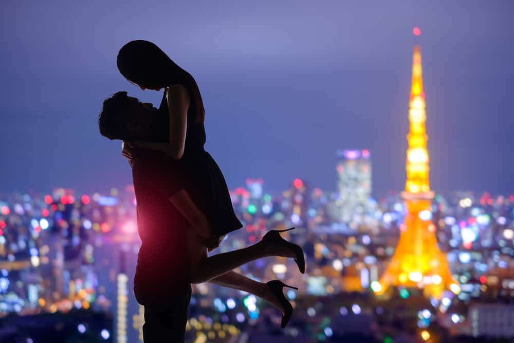 silhouette of romantic lovers with tokyo tower in japan with sunset
