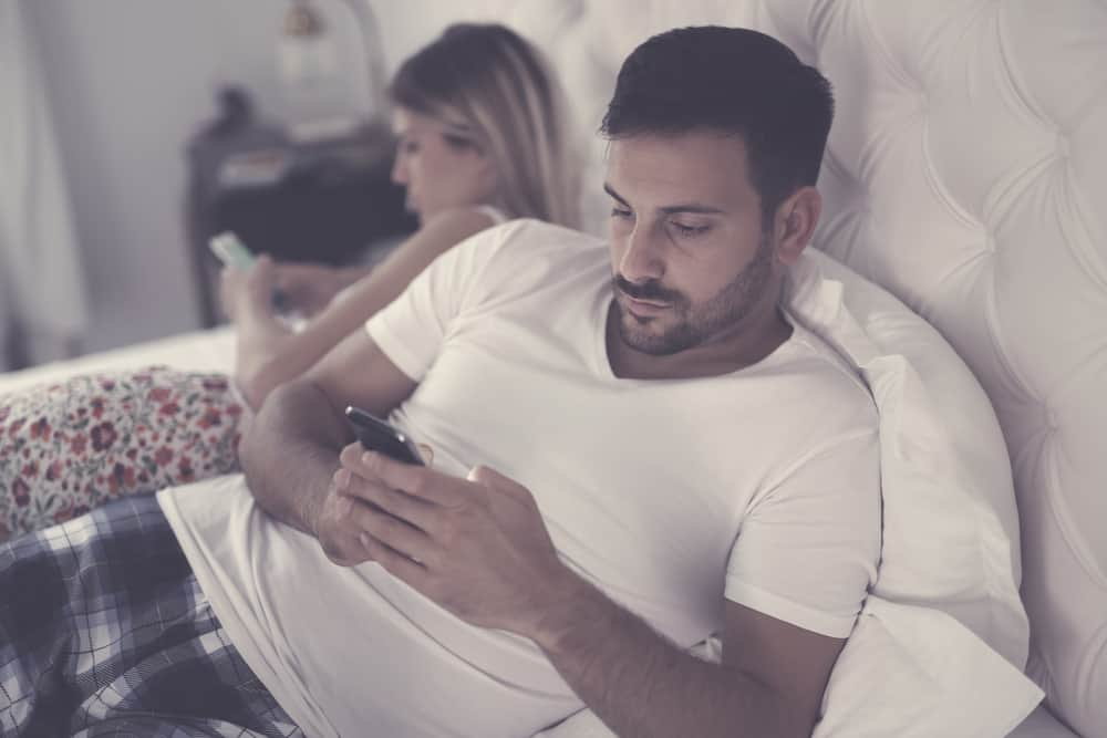 an and woman not connected, in bed on separate phones - traits of an emotionally unavailable man