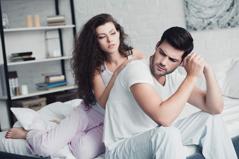 man and woman looking upset on bad - characteristics of an emotionally unavailable man main image