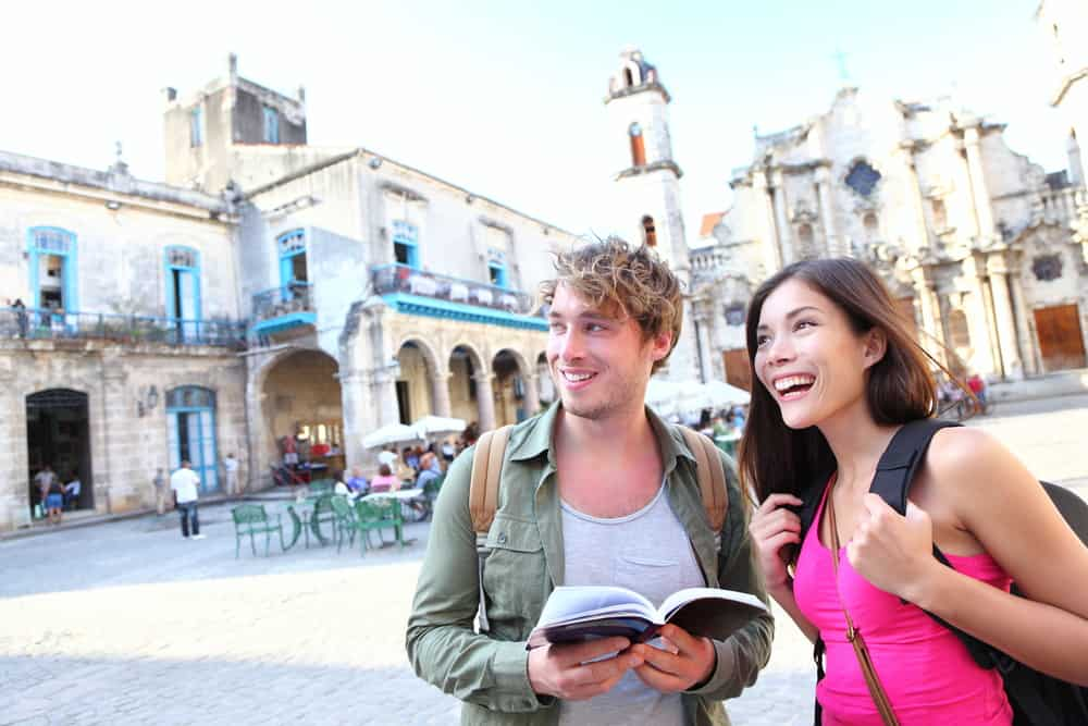 couple traveling together - smiling looking at a map in a bright european style city