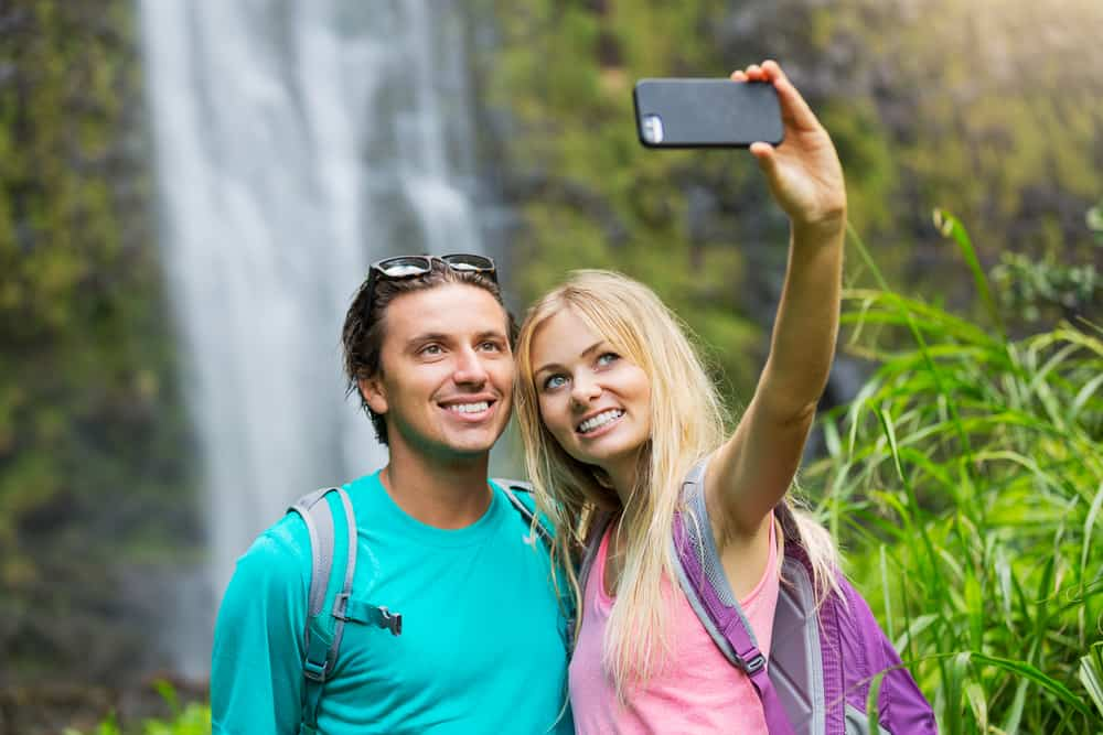 love captions for instagram header - couple smiling by waterfall
