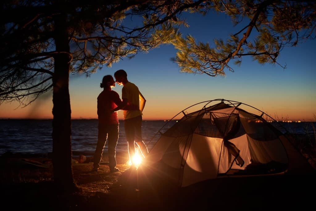 Night camping under tree at sea. Silhouettes of hiker couple, back view of man and woman stand at campfire, embracing near tourist tent in evening. Tourism, happy relations and outdoor camping concept