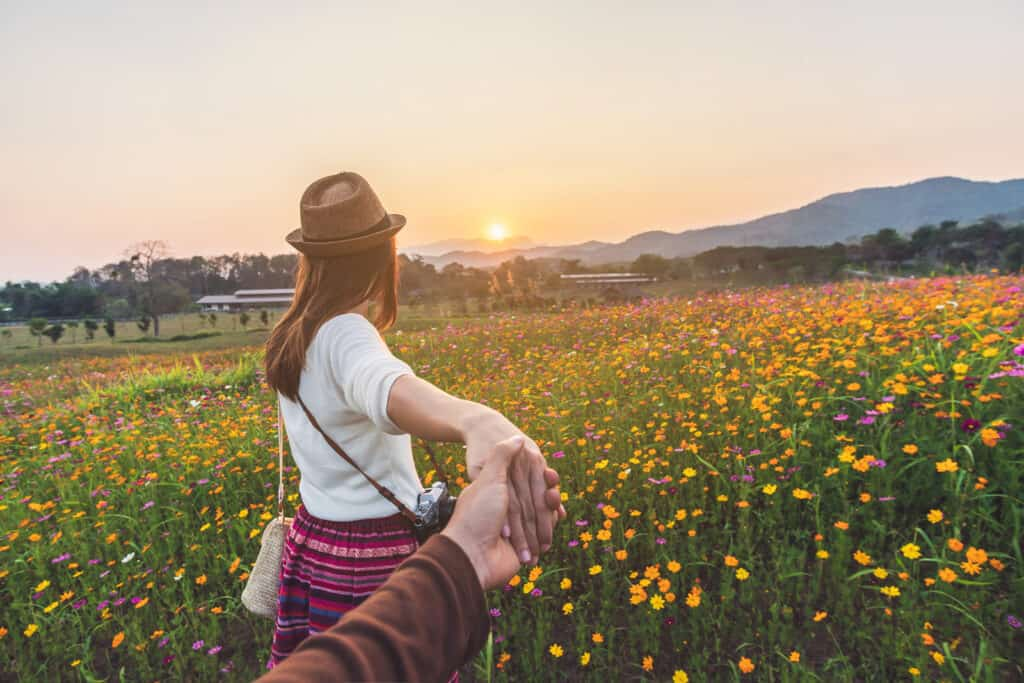 traveling as a couple tips header - woman leads man into field at sunset, holding hands