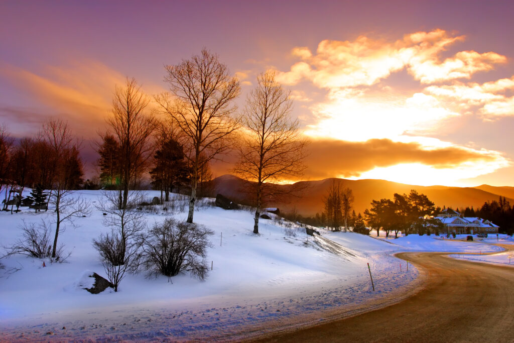 impressive sunset with purple and orange over snowy vermont mountains