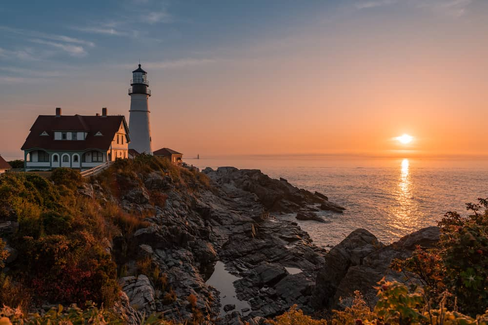 beautiful colorful sunset at the portland head lighthouse maine - perfect activity for romantic getaways in new england