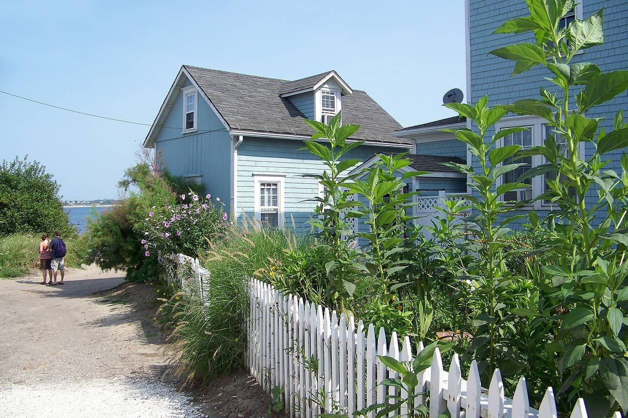 things to do on block island - blue house on block island rhode island surrounded by tall green plants