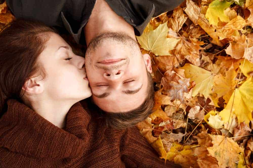 the cutest fall date ideas - couple laying on fall leaves, girl kissing boy's cheek