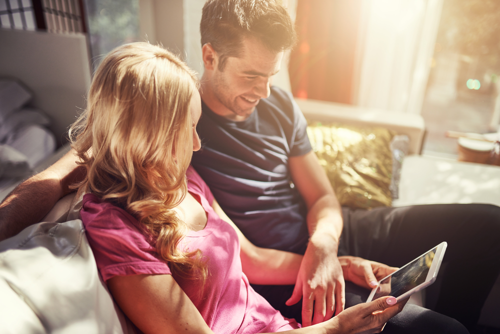 best marriage books for couples header image - couple sitting on couch together reading ipad