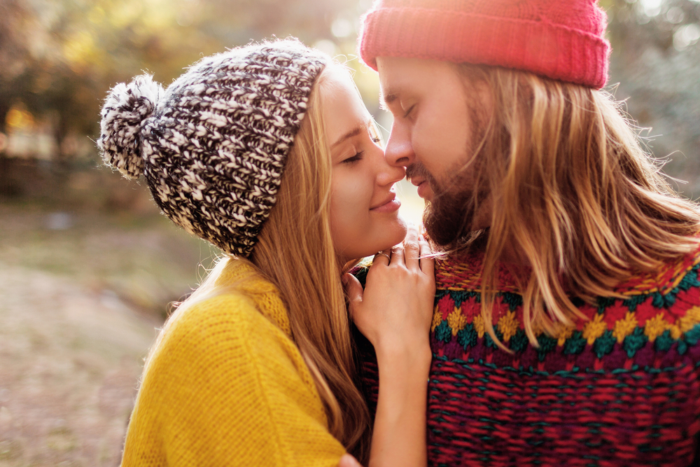 relationship rituals header image - couple in brightly colored sweaters and winter hats nuzzling outdoors in the late sun