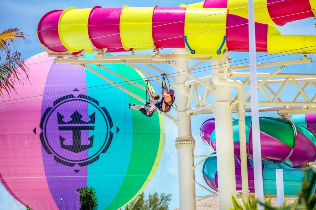 two riders zip lining in front of colorful slide and balloon